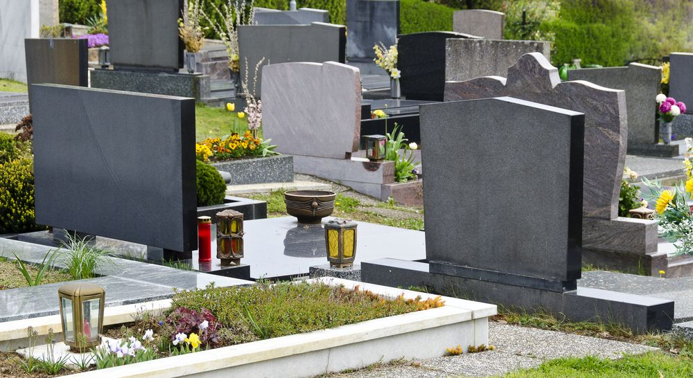 Several tombstones in a graveyard. | Source: Shutterstock
