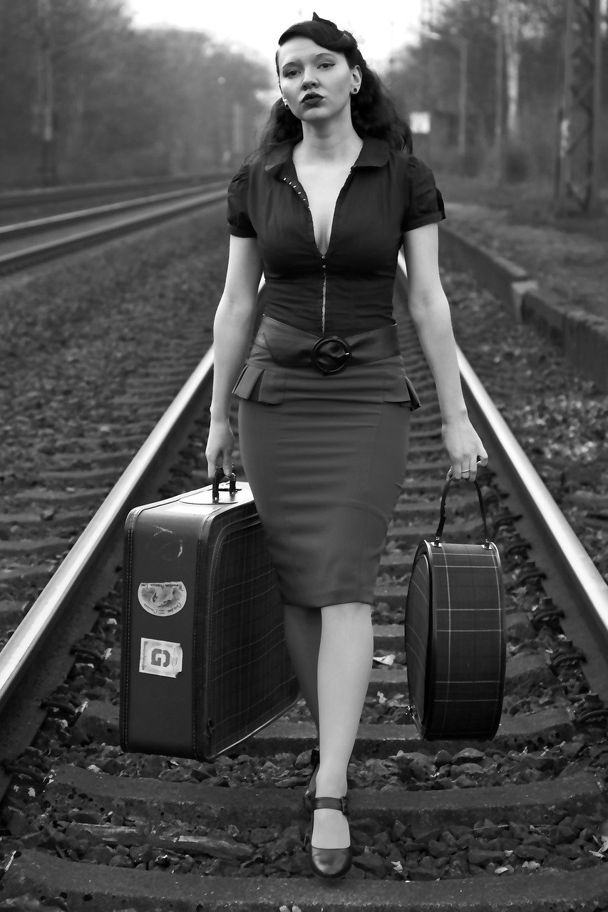 A black-and-white image of a woman carrying bags while walking on railway lines | Photo: Pixabay Juergen_G