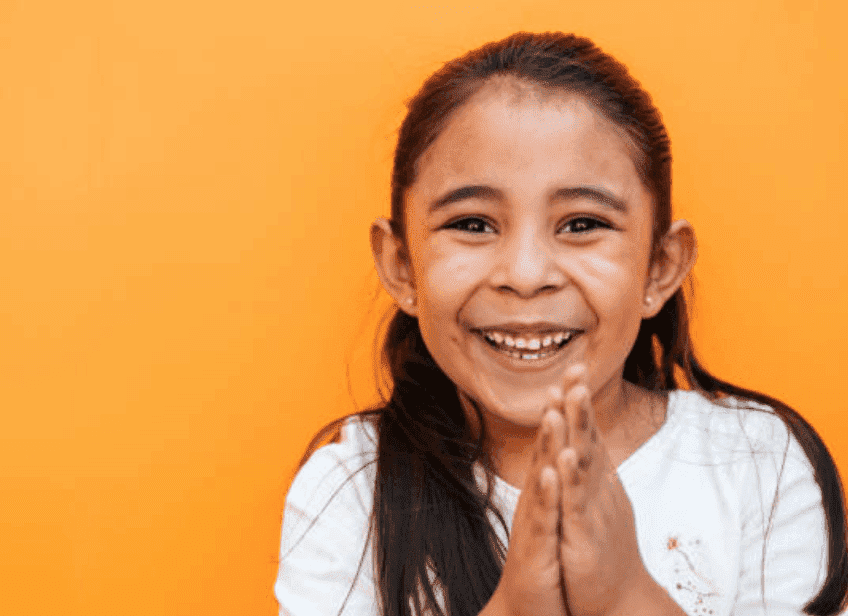 A young girl smiles as she holds her hands in together in prayer, Mexico | Source: Getty Images