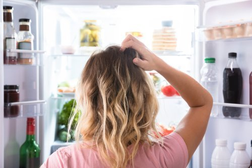 A woman looking at the contents of the fridge.   Source: Shutterstock.