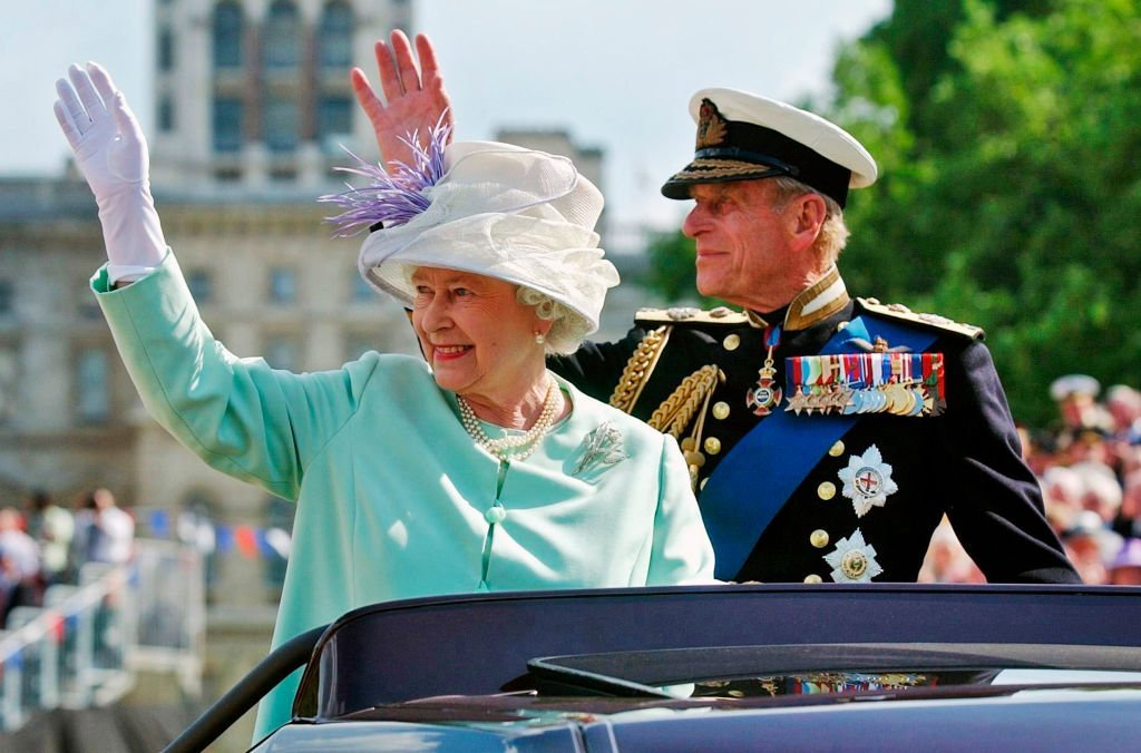 """Queen Elizabeth II and Prince Phillip the Duke of Edinburgh wave to the crowd as they leave the """"Recollections Of World War II Commemoration Show on National Commemoration Day July 10, 2005, in London. 