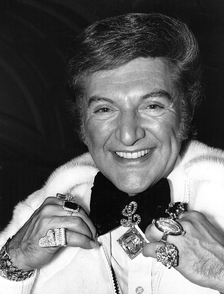 American pianist Liberace (1919 - 1987) displays his wealth of jewellery as he sweeps into London Airport.  | Getty Images