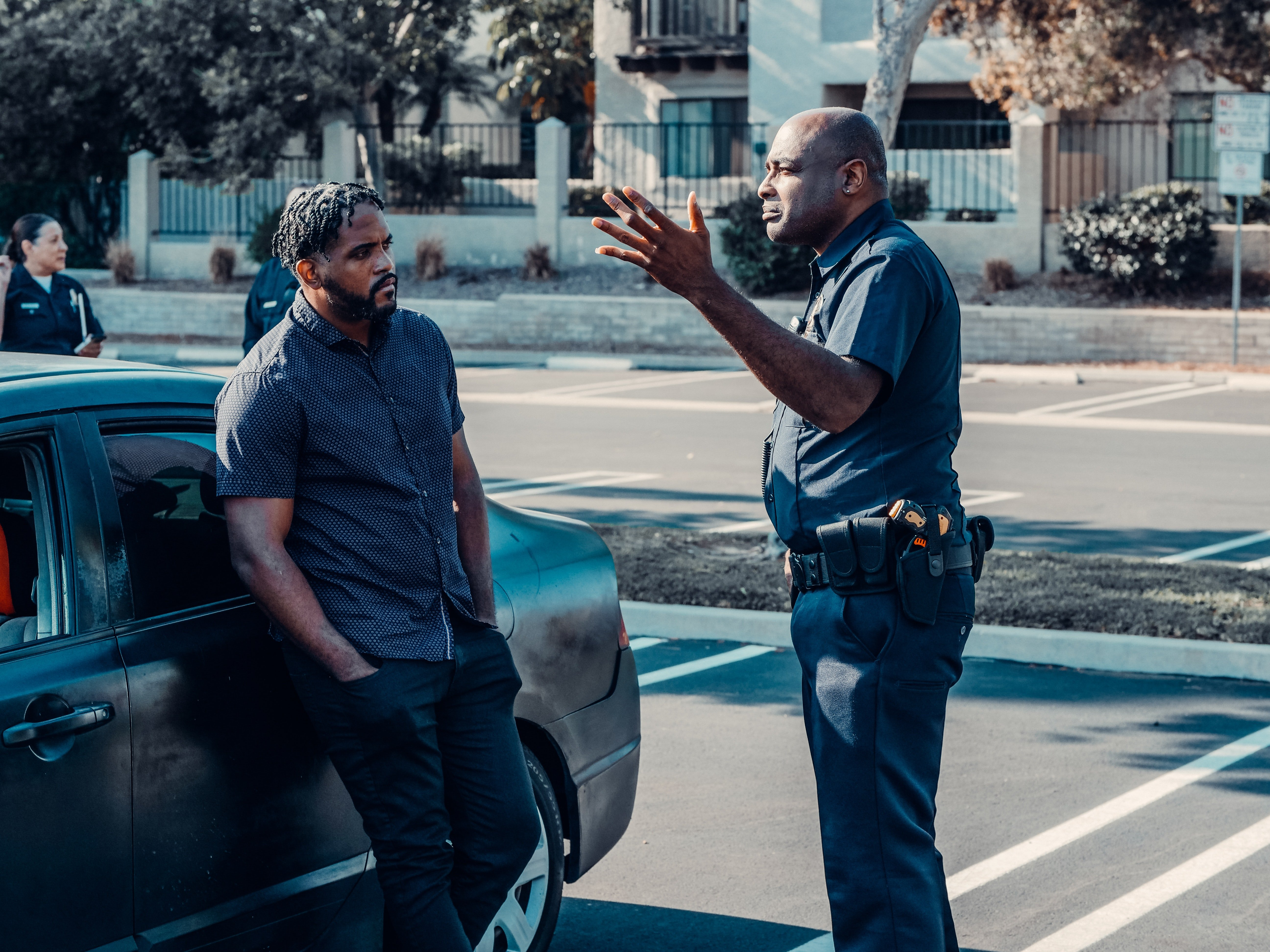 An officer talking to a man leaning against a car. | Pexels/ Kindel Media