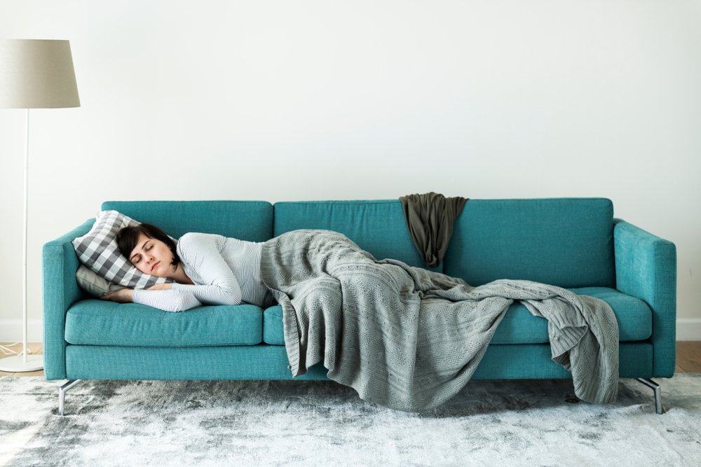 A woman sleeping comfortably on a couch | Photo: Shutterstock/Rawpixel.com