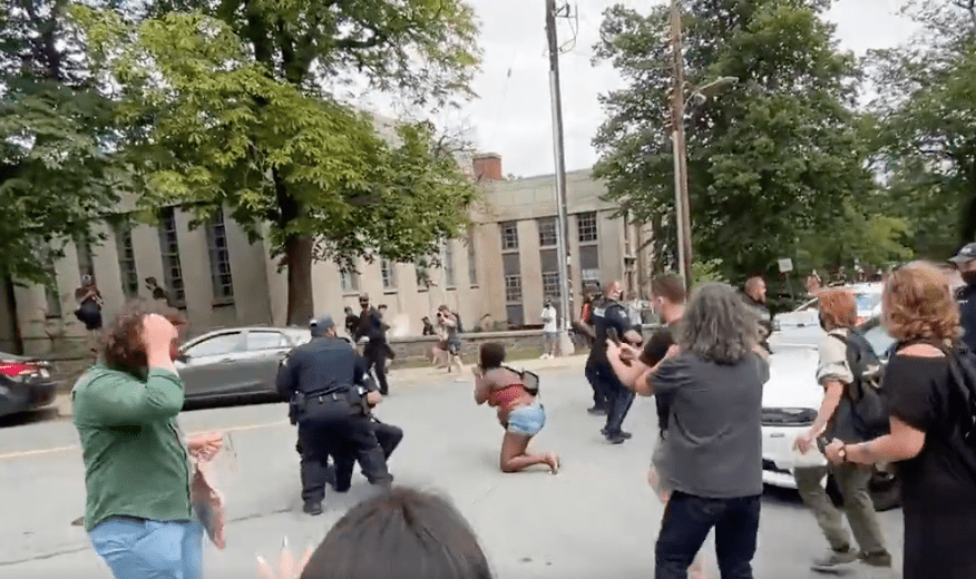 Protestors run across the street as police take action against them | Photo: Twitter/zwoodford