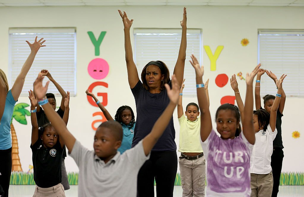 "Michelle Obama participating in a children's yoga class in celebration of the fourth anniversary of ""Lets Move!"" in 2014. 