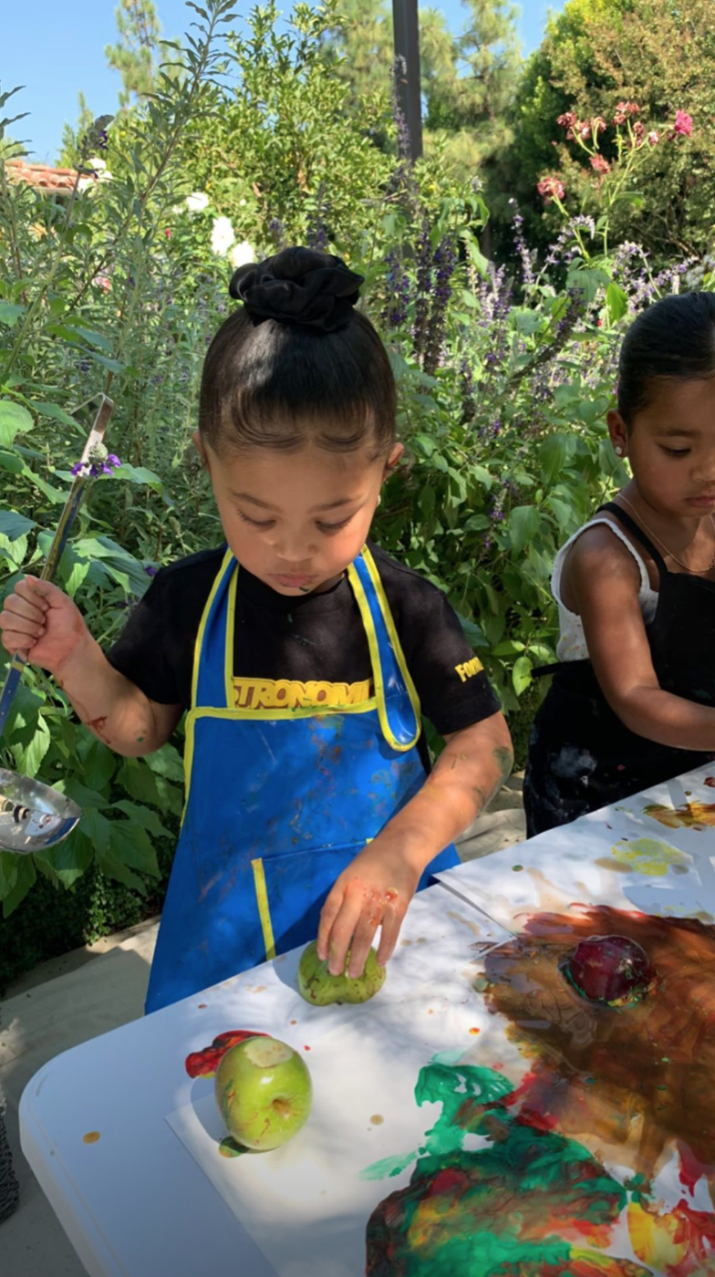Stormi Jenner and True Thompson enjoy painting during their first day of pre-school. | Source: Instagram/kyliejenner