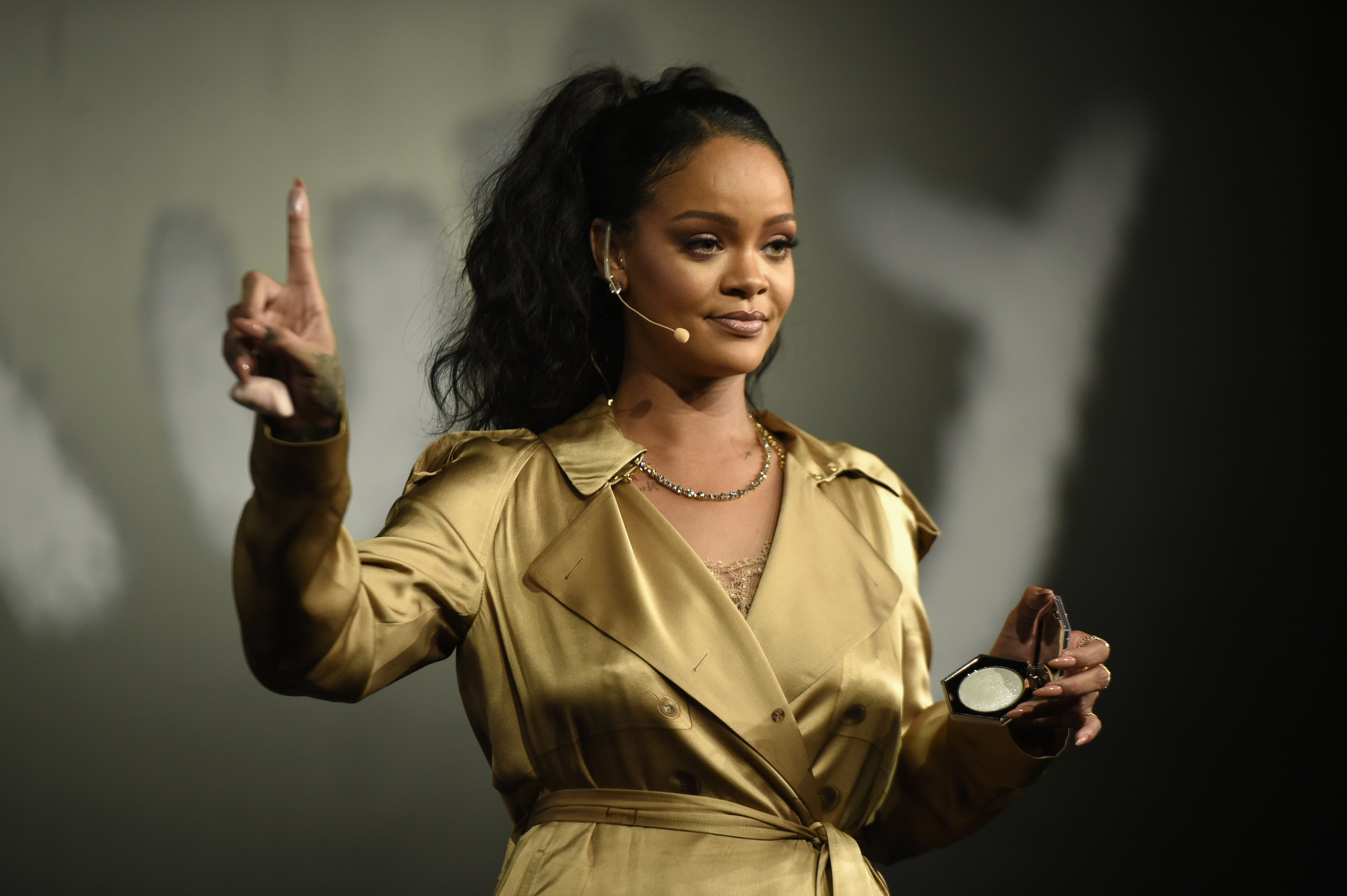 """Rihanna gestures on stage during her Fenty Beauty talk in collaboration with Sephora, for the launch of her new Stunna Lip paint """"Uninvited"""" on September 29, 2018. 