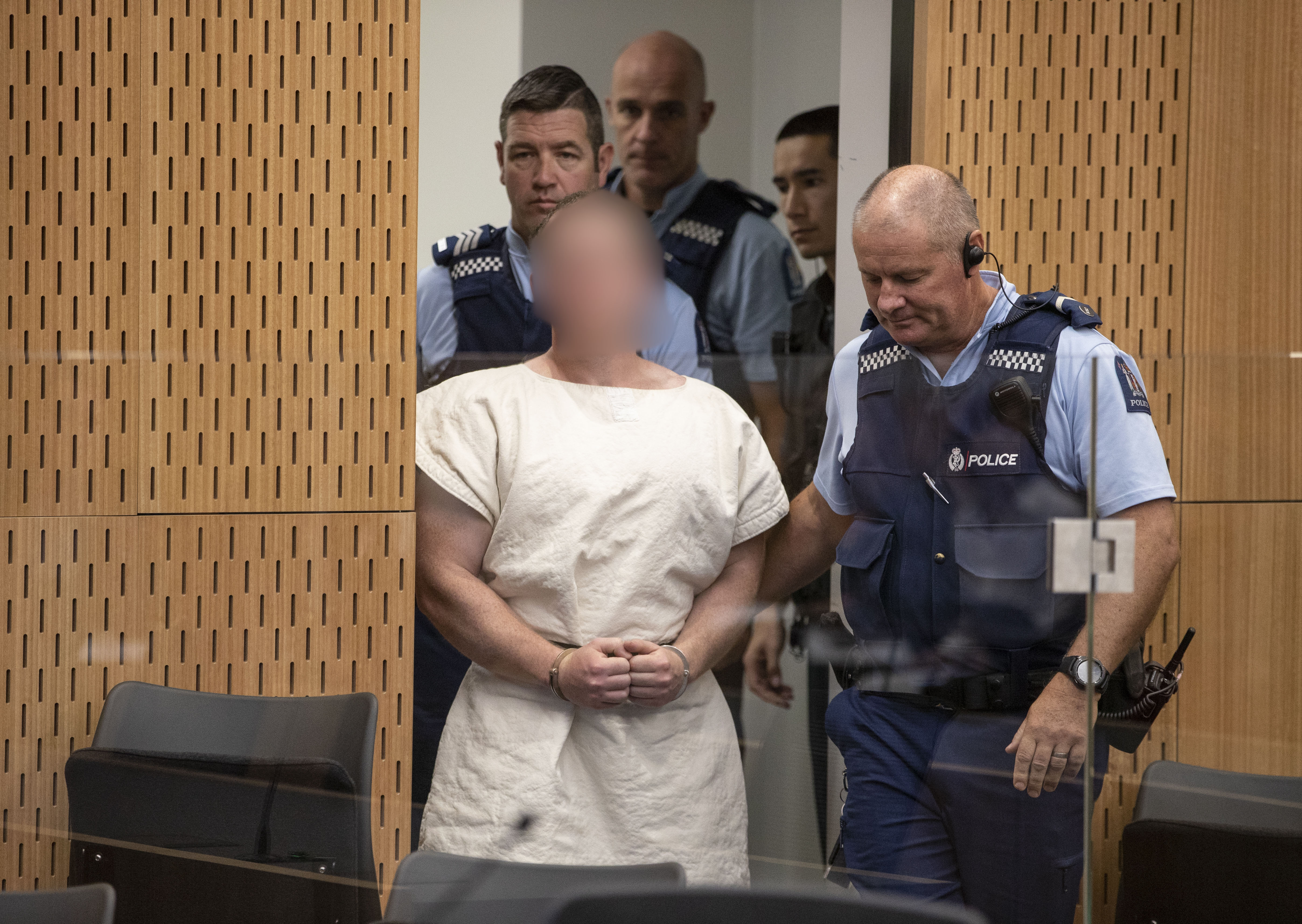 Brenton Tarrant being led into the courtroom by several police officers at the Christchurch District Court | Photo: Getty Images
