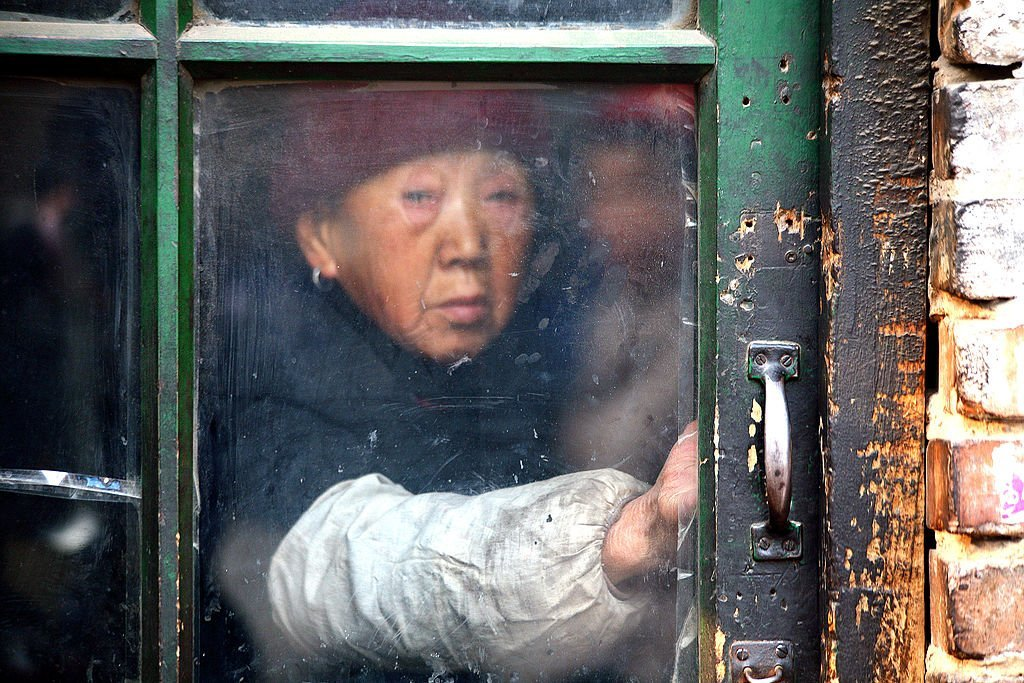An old woman holds onto the windowpane as she looked out, on December 27, 2008 | Source: Getty Images