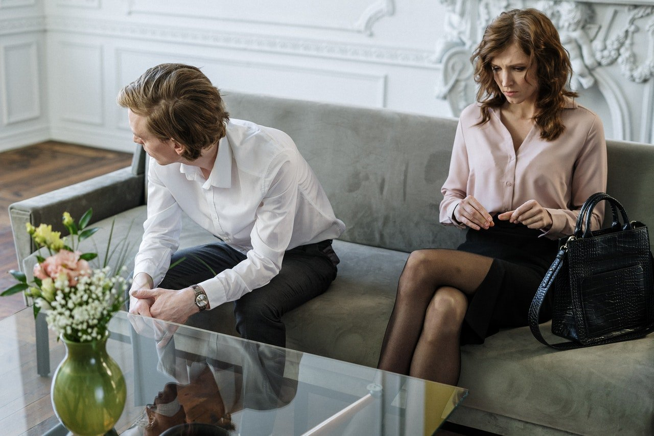Man and woman sitting on a couch after an argument   Source: Pexels
