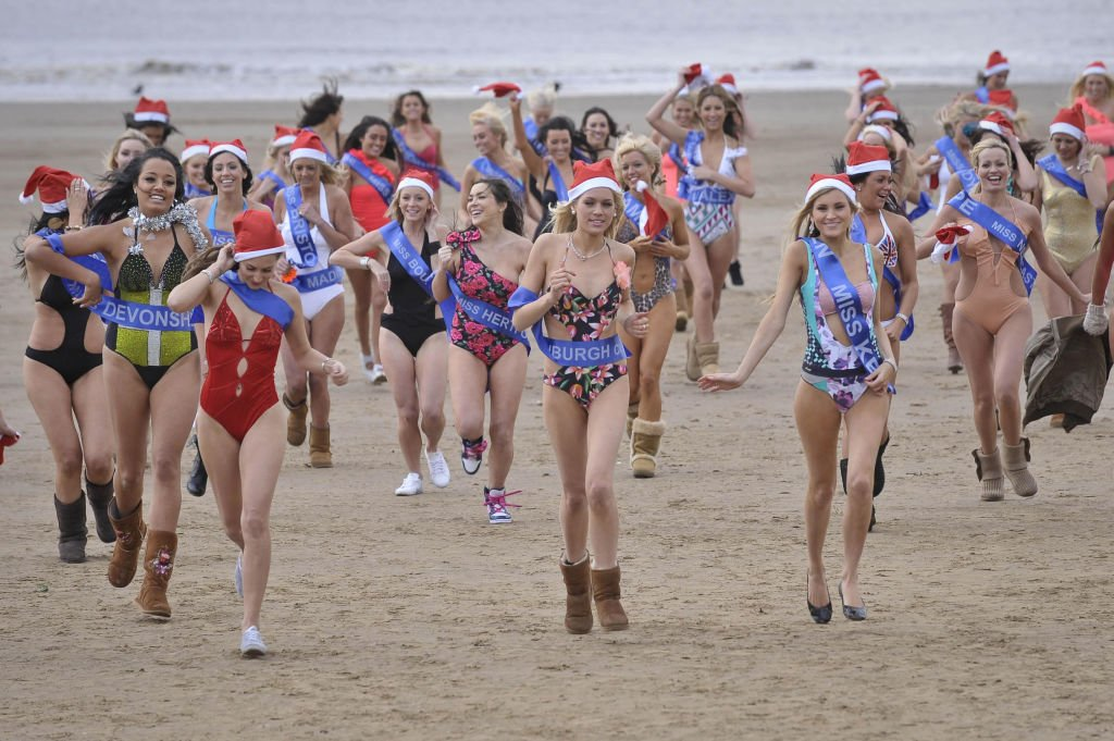 Finalists of the Miss Great Britain beauty pageant run on the beach wearing one piece swimsuits on December 10, 2020. | Photo: Getty Images