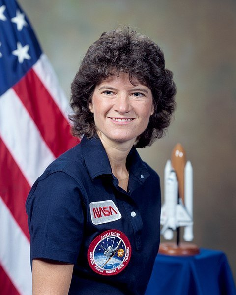 Portrait of Sally Ride in NASA uniform with U.S. flag in the background | Source: Wikimedia Commons