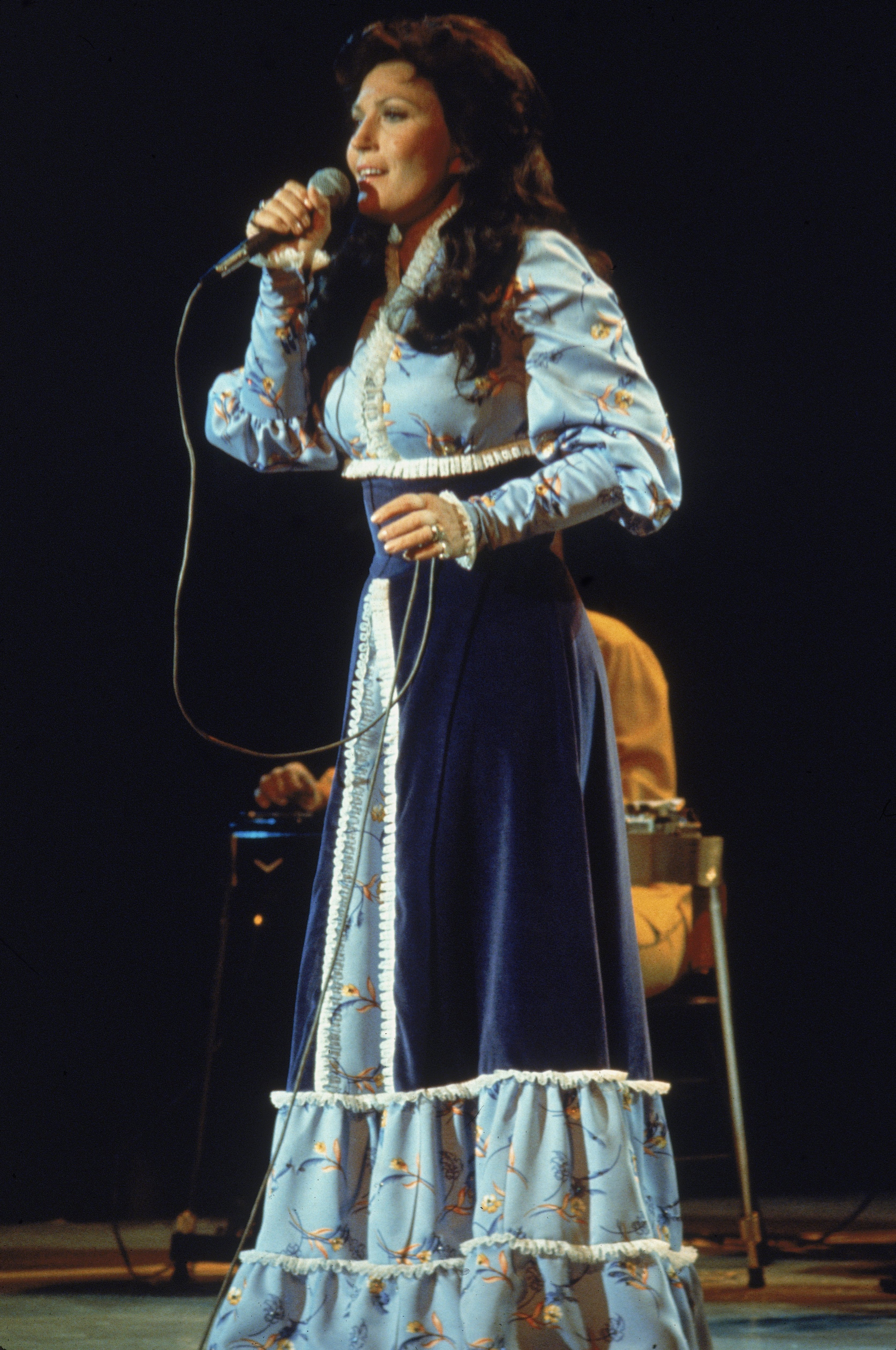 Loretta Lynn performs on stage, wearing a long dress, circa 1980. | Source: Getty Images.