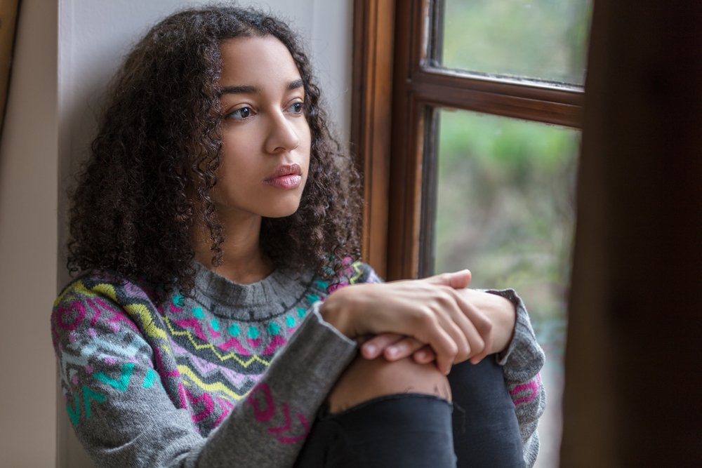 A photo of a sad teenager looking out of a window. | Photo: Shutterstock