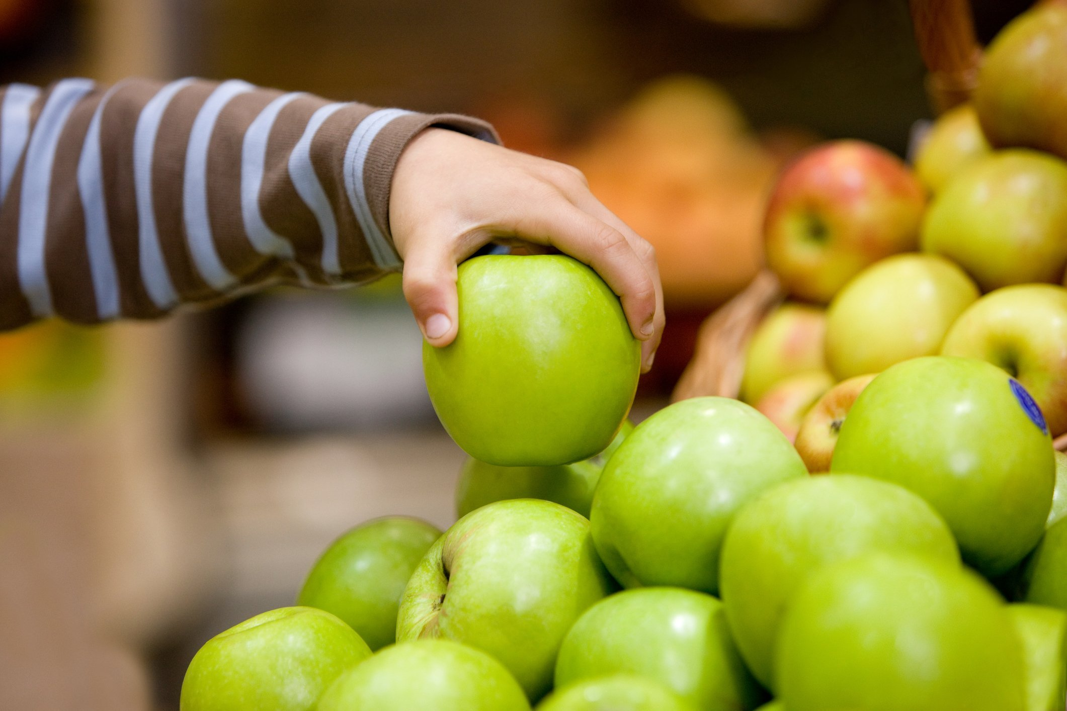 An image showing a child's hand holding an apple   Photo: Getty Images