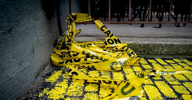 A pile of used police tape, lays against a cement floor and wall. | Photo: Shutterstock