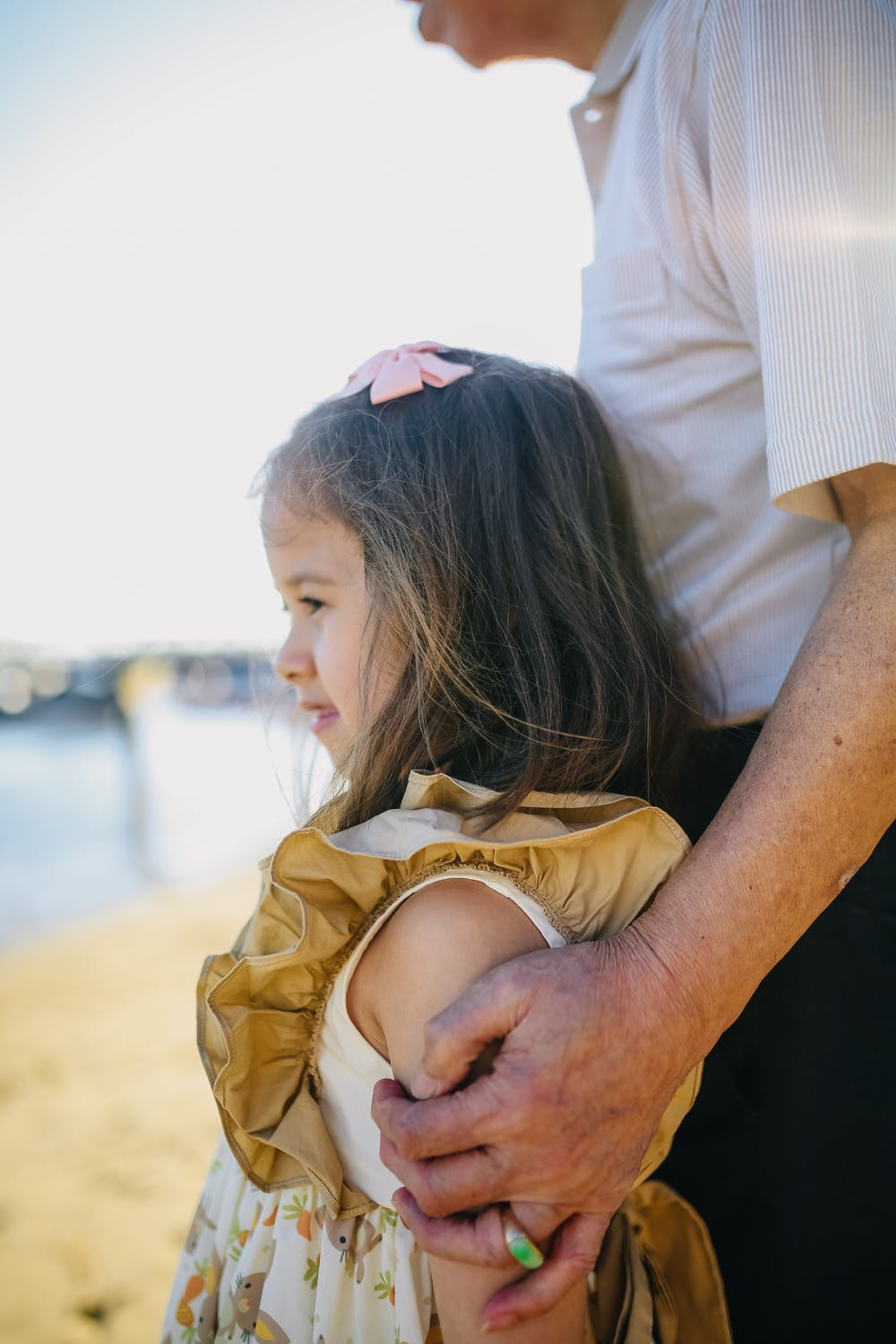 A little girl leaning against an old man. | Photo: Pexels
