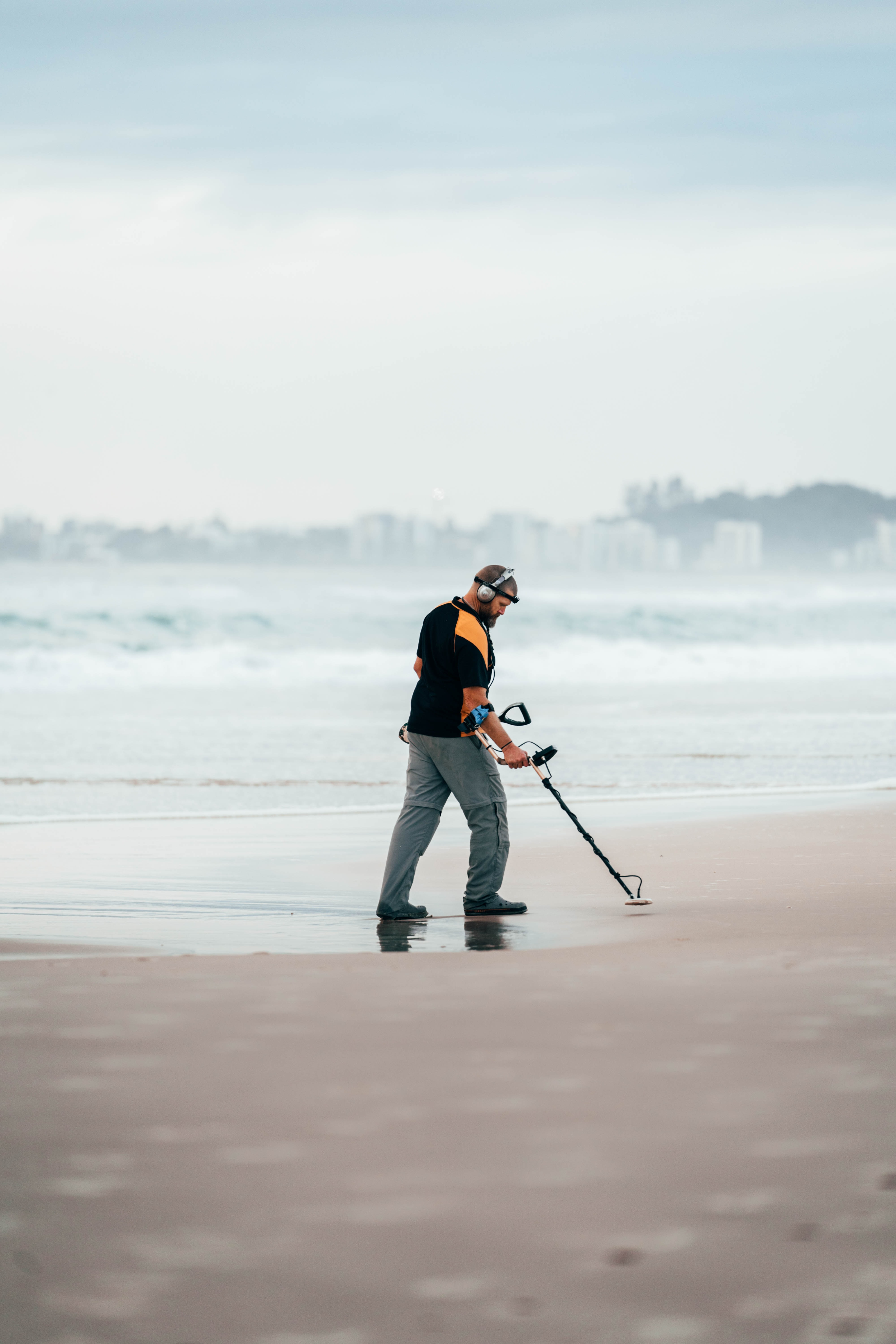 A man uses his metal detector on a beach   Photo: Unsplash/Carnaby Gilany