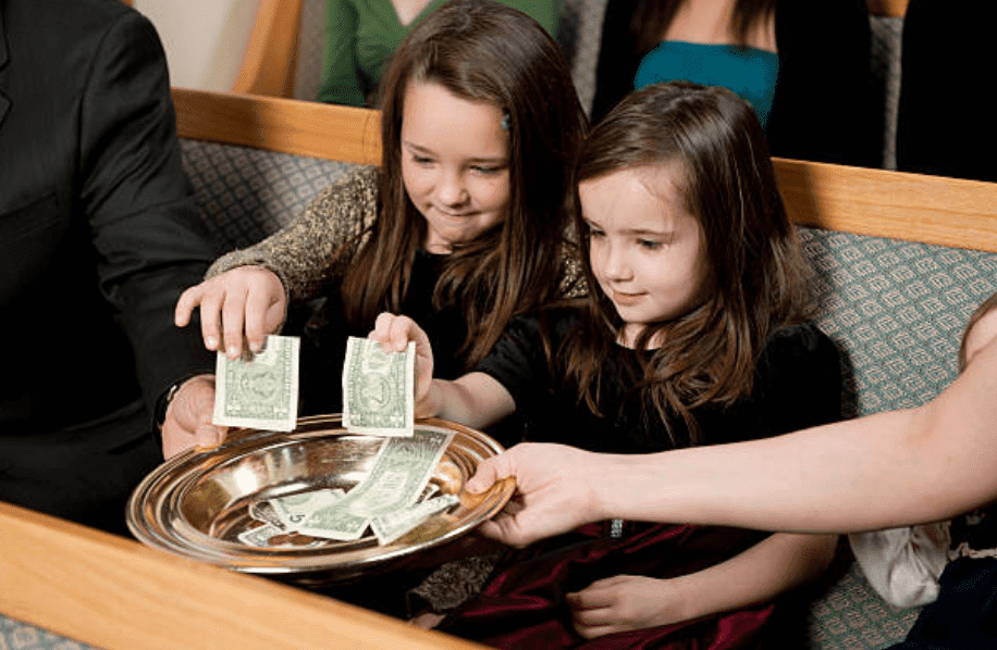 Two young girls give money offerings in church | Source: Getty Images