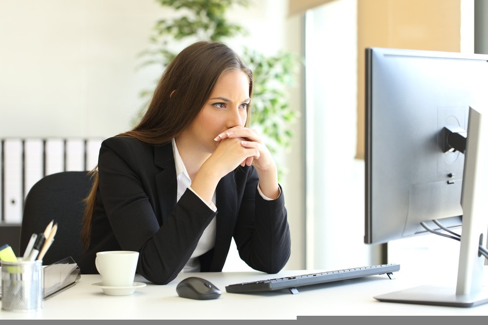 A working woman deeply thinking about something while looking at her desktop. | Source: Shutterstock
