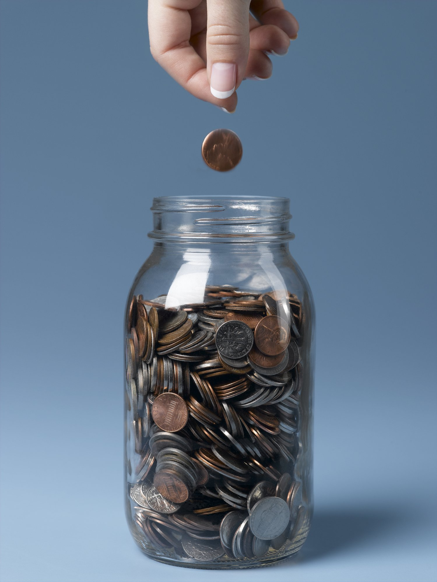 Woman dropping coin into jar close-up | Photo: Getty Images