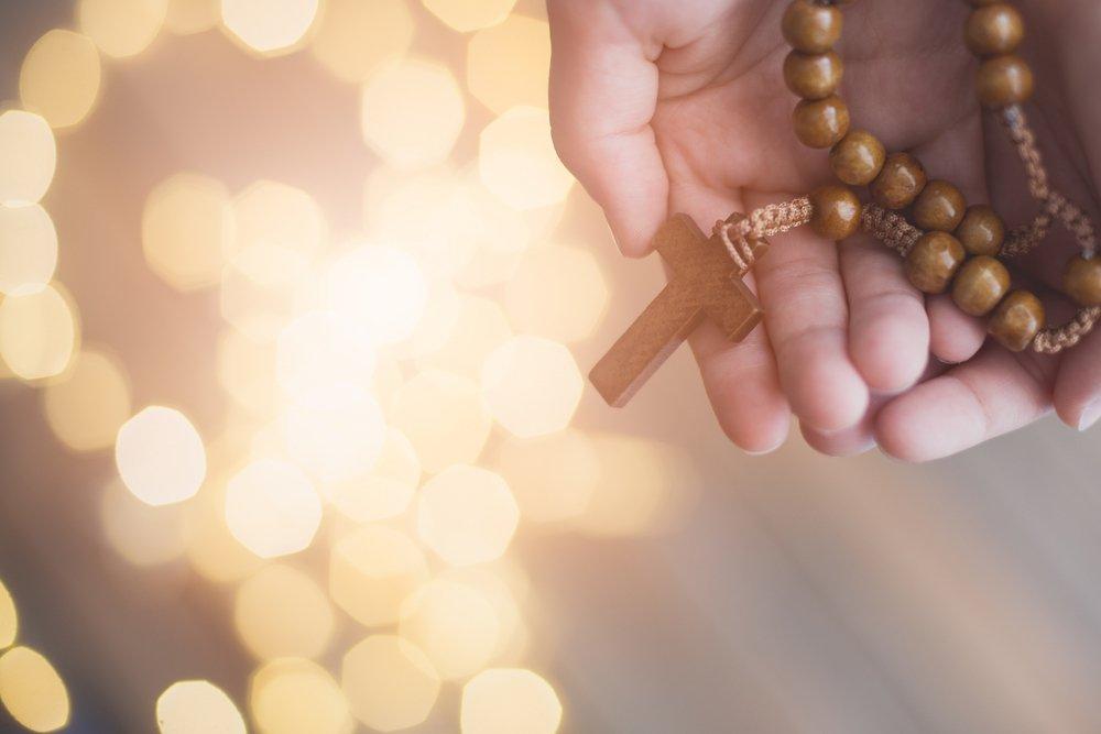 Persona con un rosario en sus manos.| Fuente: Shutterstock