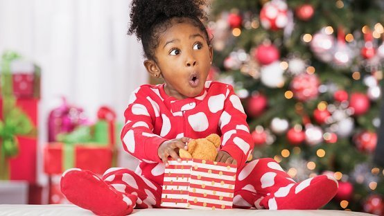 Surprised girl holding a wrapped gift on Christmas | Photo: Getty Images