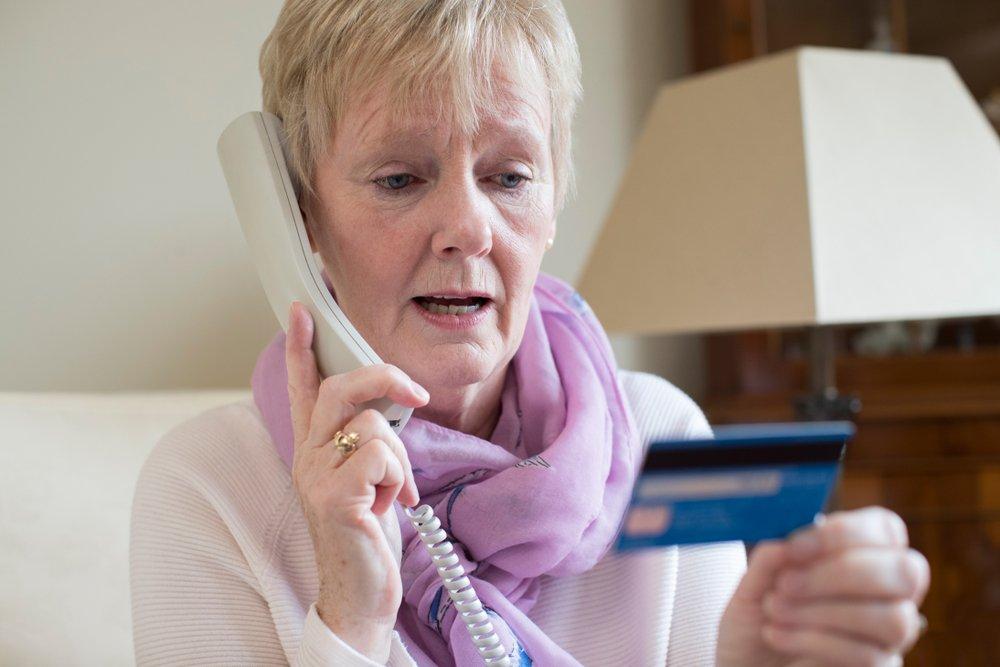 Mujer mayor dando datos de su tarjeta bancaria por teléfono. Fuente: Shutterstock