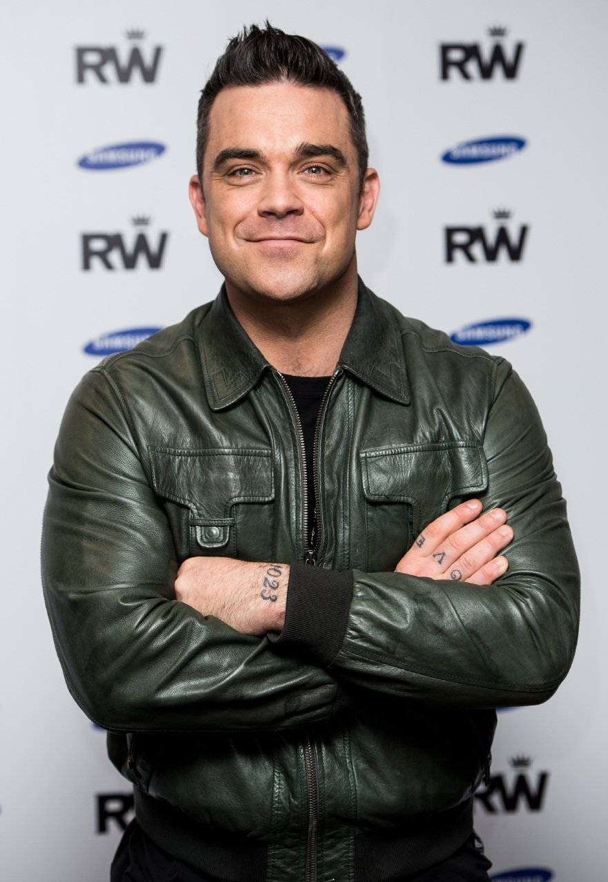 Robbie Williams attends a photocall to announce a forthcoming stadium tour for Summer 2013. | Source: Getty Images