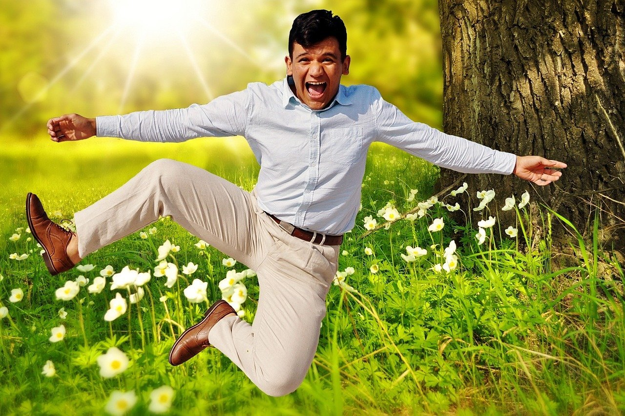 A formally dressed man jumping in the air for joy with greenery in the background   Photo: Pixabay/Alexas_Fotos