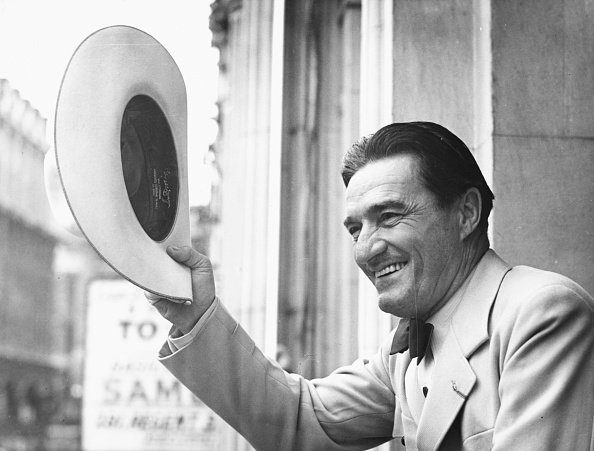 Actor Tom Mix seen waving his cowboy hat from the balcony of the London Palladium on August 31st 1938. | Photo: Getty Images