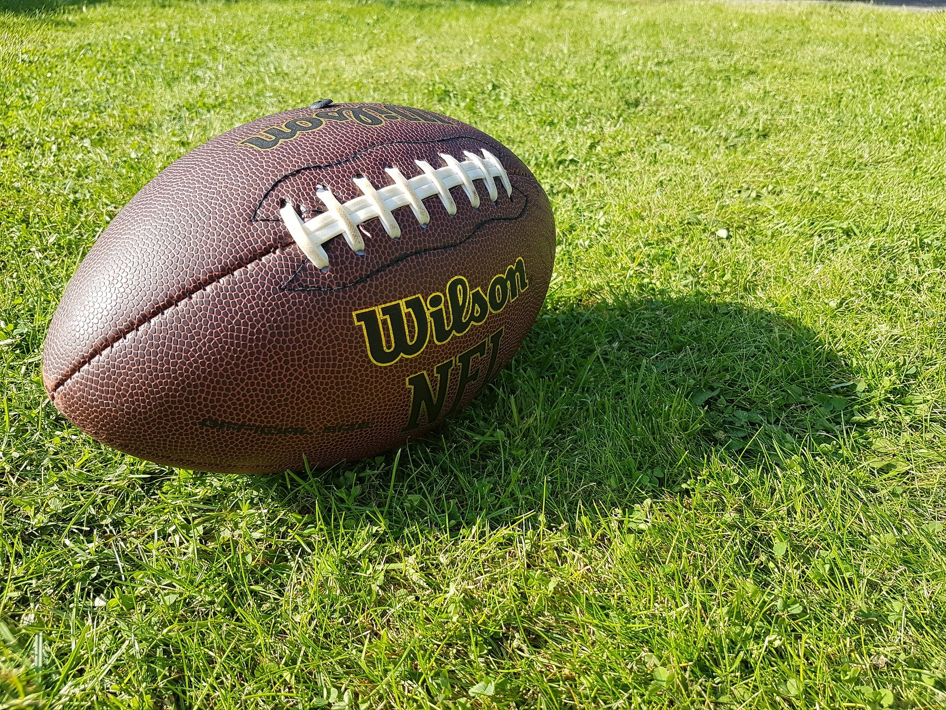 A football on a field. | Photo: Pixabay/Oliver Cardall