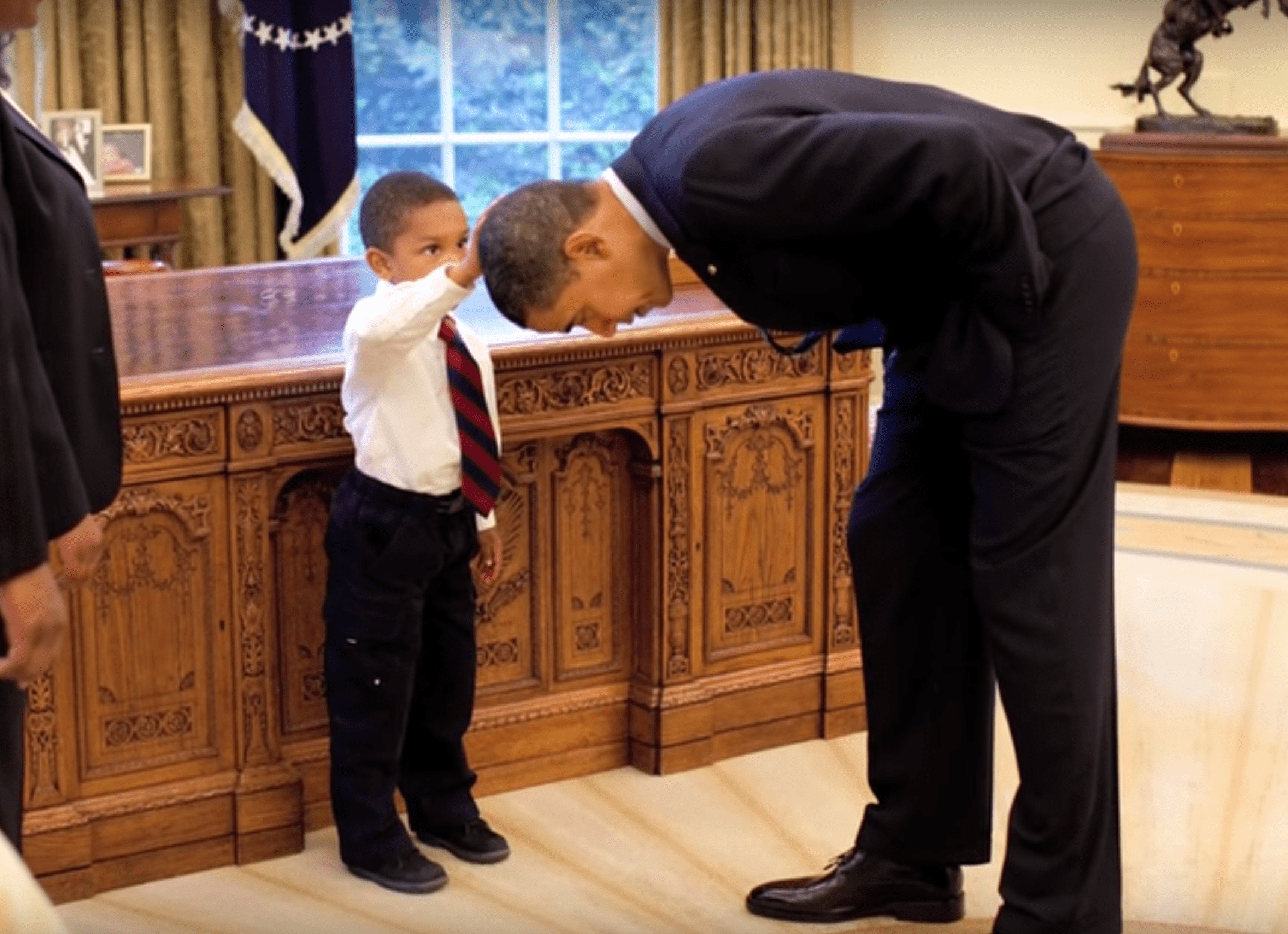 Obama bends down to let a young boy touch his head. | Source: YouTube/washingtonpost
