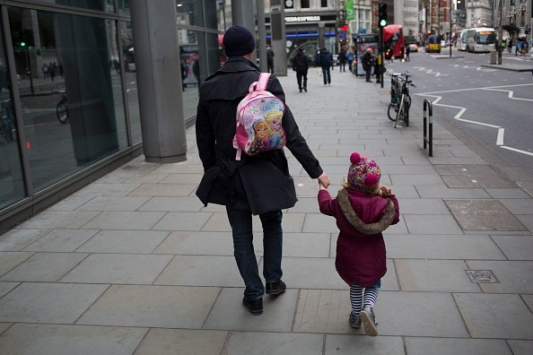 Father carries his daughter's Anna and Elsa Frozen backpack | Photo: Getty Images