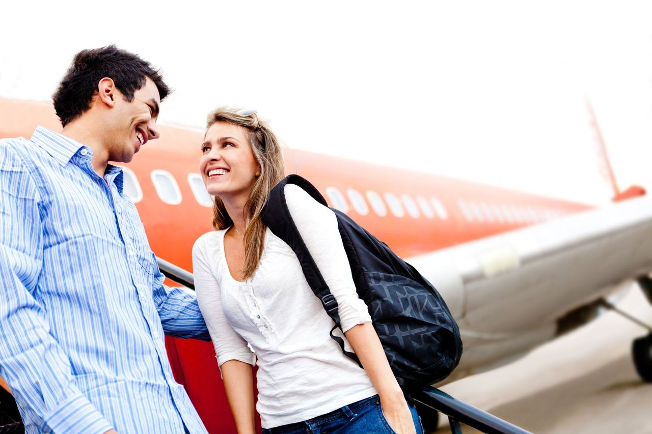 A couple smiling at each other in front of a plane. | Source: Shutterstock