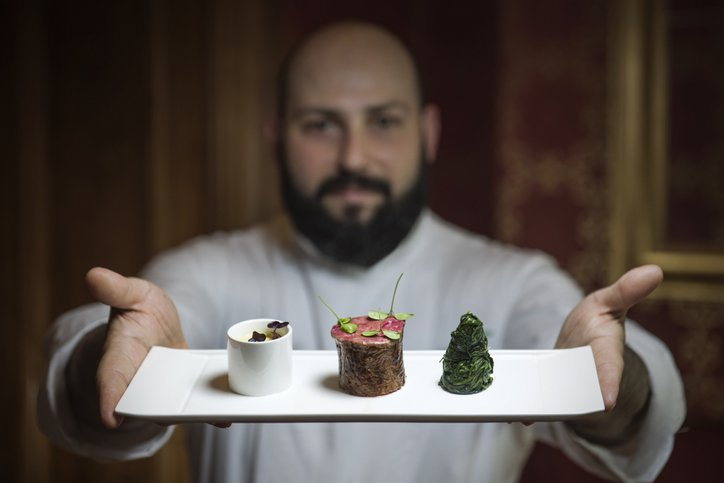 Chef carrying a plate of food | Photo: Getty Images