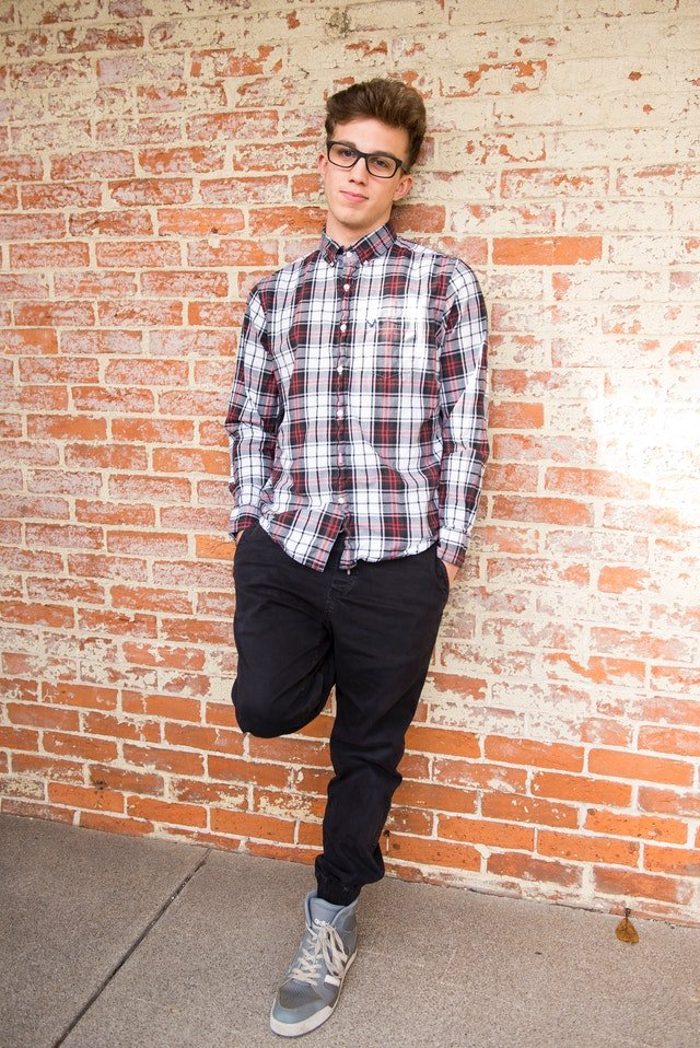Boy wearing red and white plaid shirt and black pants leans against wall | Photo: Pexels