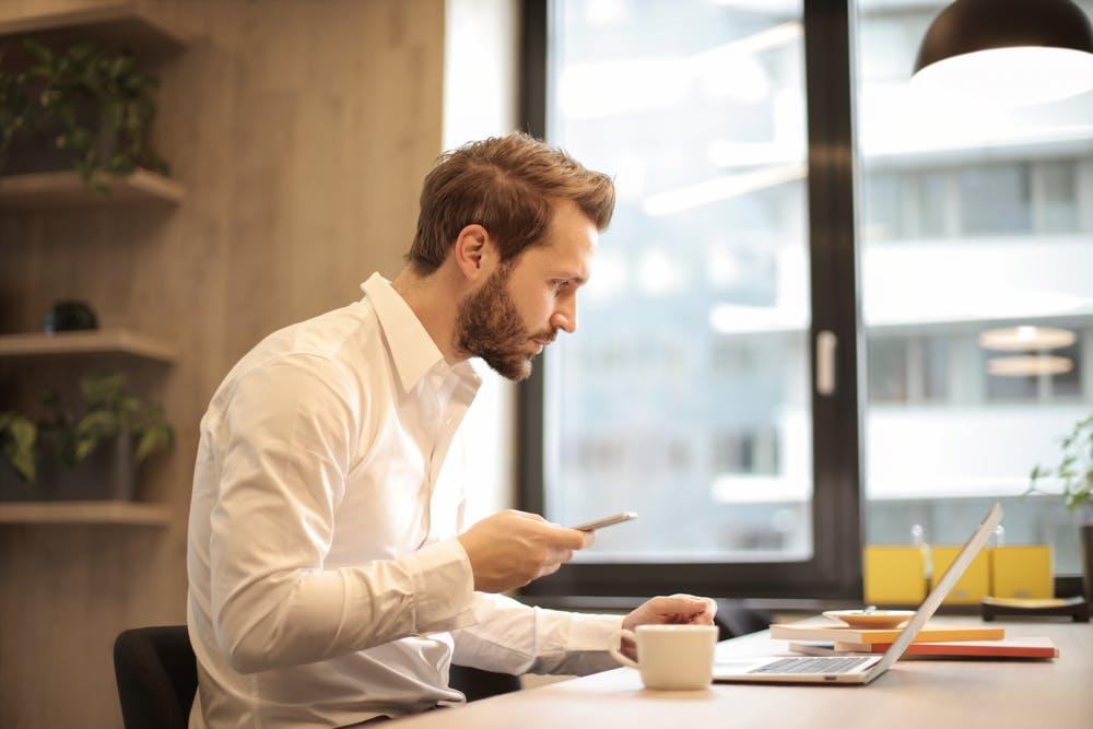 Un homme lisant un message texte alors qu'il était au bureau. | Pexels