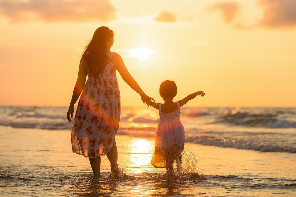 A woman and mother walking on the beach into the sunset. | Photo: Pixabay