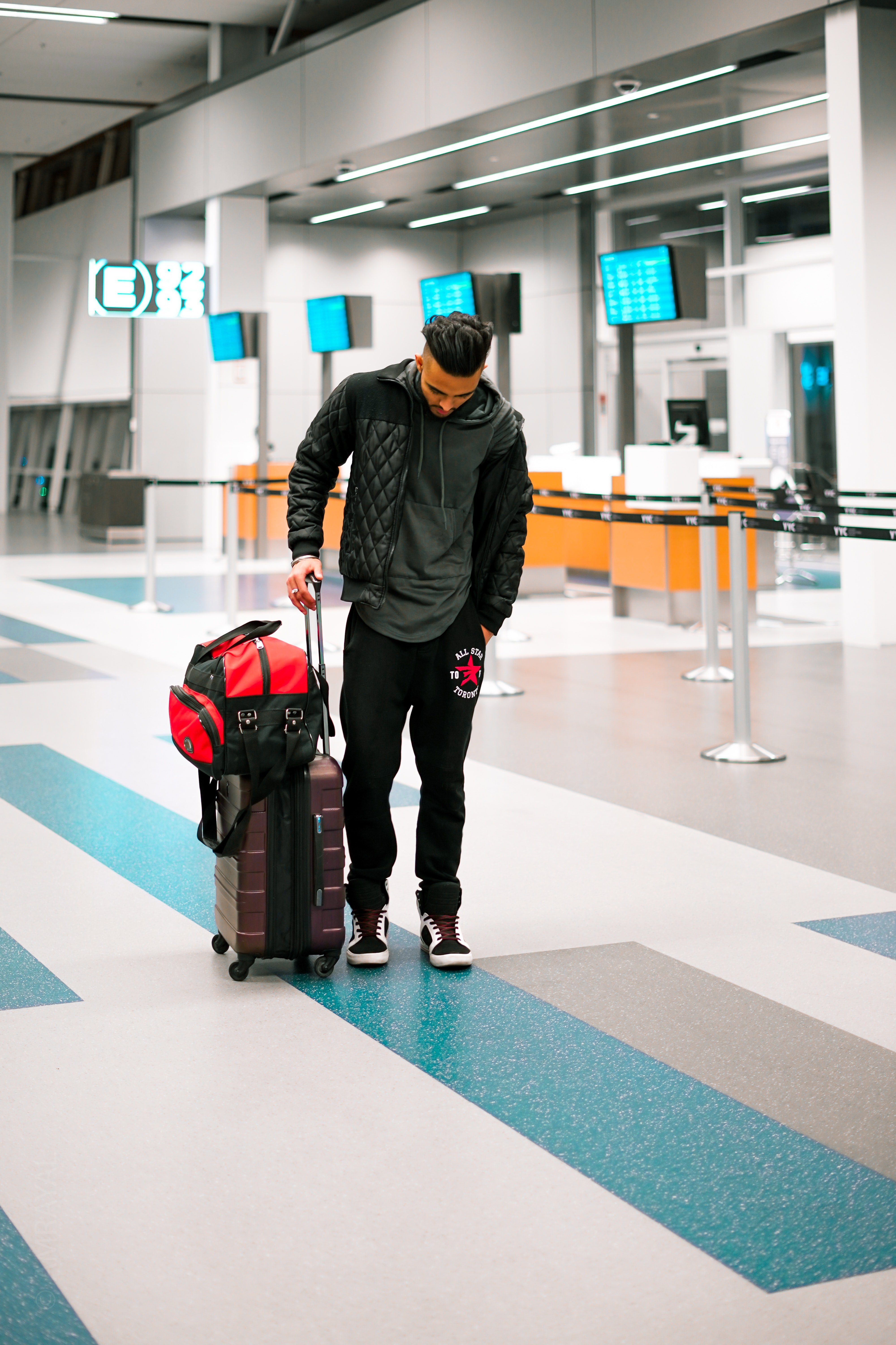 Pictured - A man at the airport carrying his luggage while looking down. | Source: Pexels