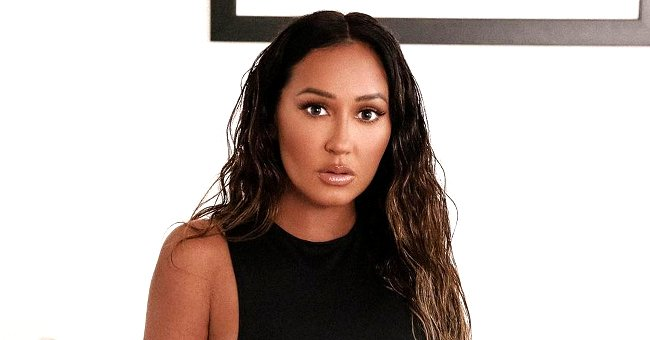 Adrienne Bailon Shows off Stunning Weight Loss Lounging in a Black Top & White Pants
