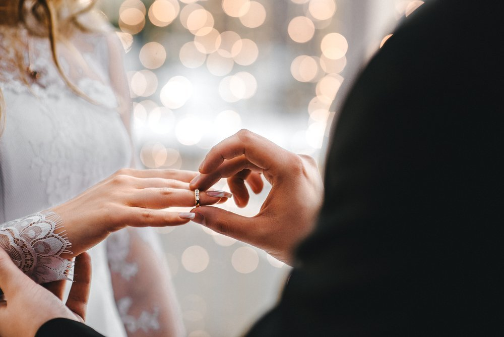 A couple exchange rings during their wedding ceremony | Shutterstock