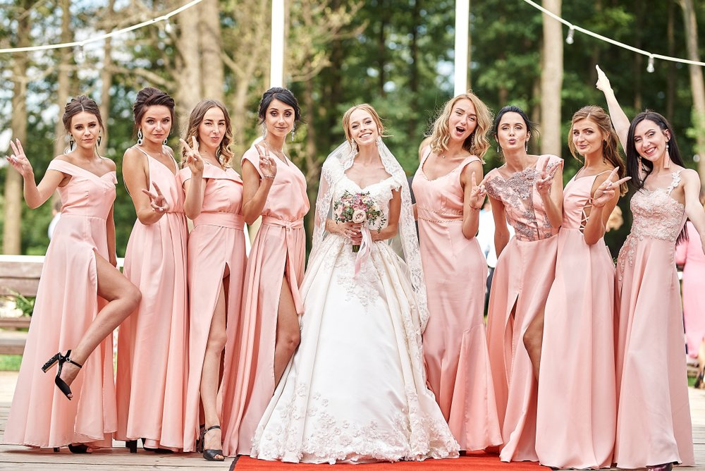 A beautiful bride and her bridesmaids posing on the park on the wedding day. | Photo: Shutterstock.