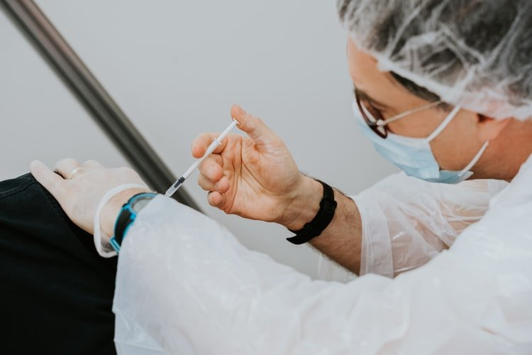 Un homme qui se fait vacciner. | Photo : Unsplash
