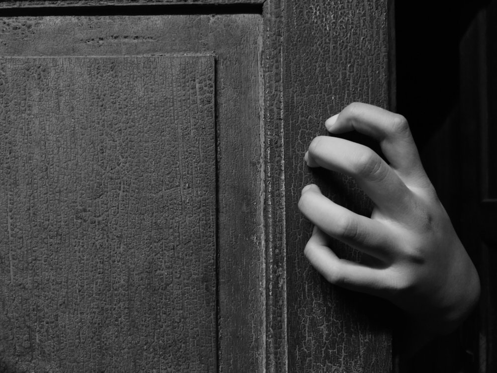 Hand holding an old door. | Photo: Shutterstock
