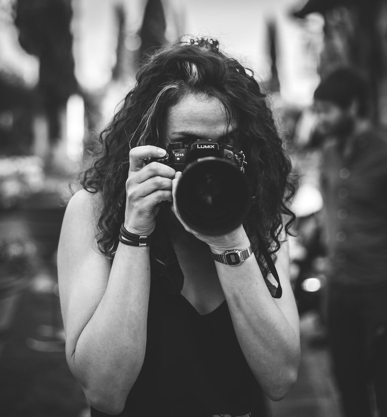 A lady trying to take a photo with a camera | Photo: Unsplash