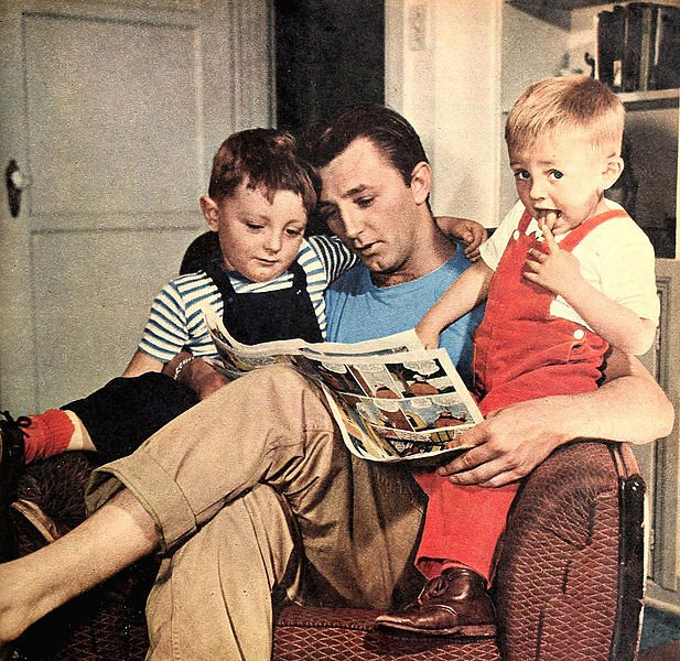 Robert Mitchum at home reading with his two sons, James Mitchum and Christopher Mitchum. | Source: Wikimedia Commons