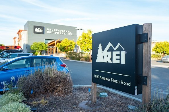 Close-up of sign for Recreational Equipment Incorporated (REI) outdoor clothing store, with facade of store in background, in Dublin, California, July 23, 2018 | Photo: Getty Images
