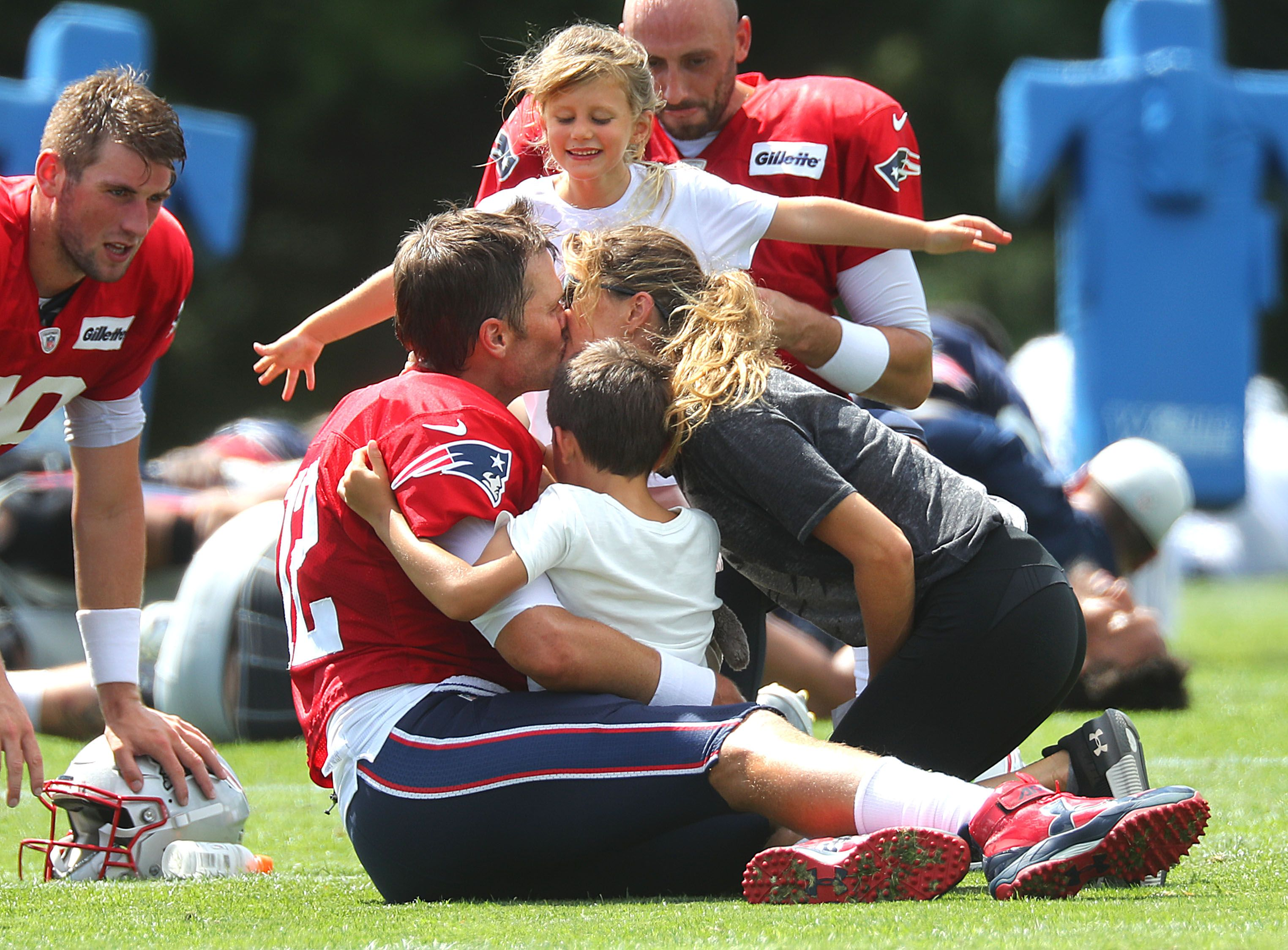 Brady gets a group hug from his daughter Vivian, son Benjamin and his wife Gisele Bundchen following Patriots training camp at the Gillette Stadium practice facility in Foxborough, MA on Aug. 3, 2018. | Source: Getty Images